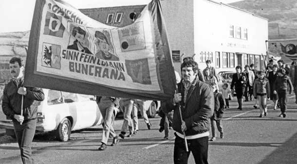 Volunteer Réamonn Mac Lochlainn (right) carries a banner at an anti-extradition demonstration in Buncrana in 1984