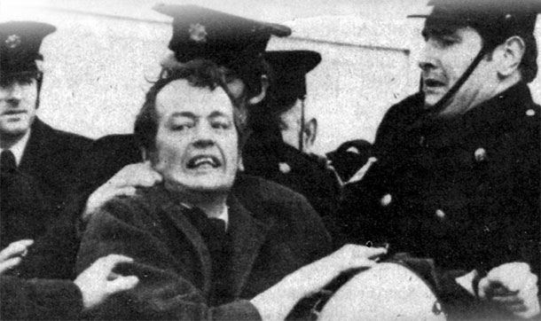 Seán Stagg, overcome with grief, is manhandled  by Gardaí at Shannon Airport as the remains of his brother are snatched