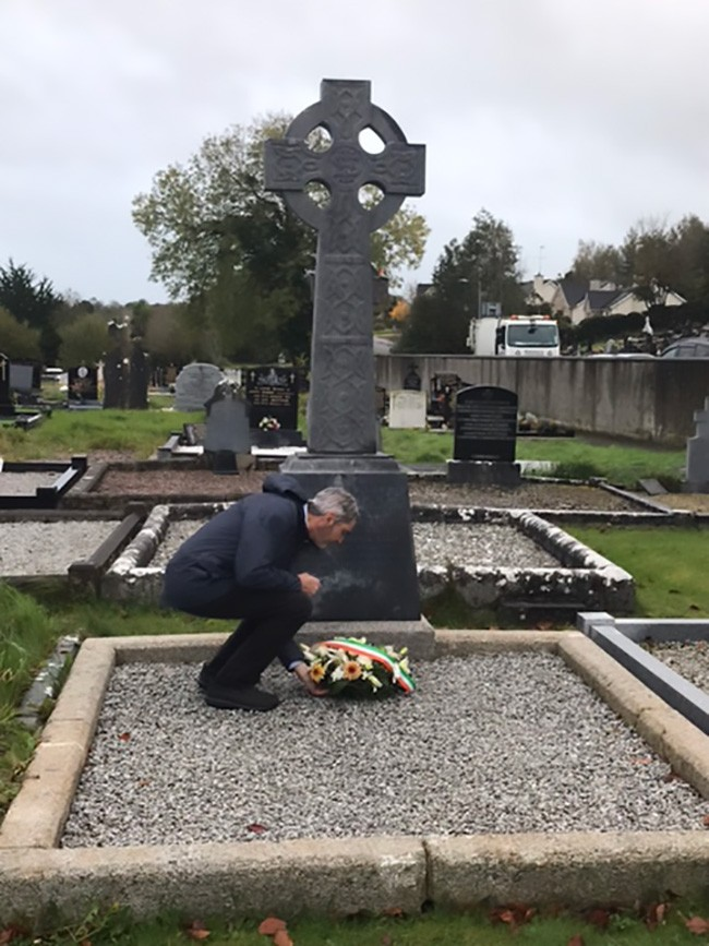 Cllr. Seán Conlon laying a wreath at the memorial to Vol. Michael Kelly in Latlurcan cemetery. Members of the Kelly family attended