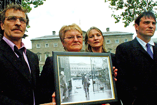 Fullerton Family - Albert (son), Dinah (wife), Amanda (daughter) and Eddie Jnr (son) outside Leinster House, carrying a 1984 photo of Eddie leaving Leinster House after a Labour Minister objected to his presence on a council delegation from Donegal