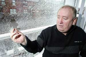 Fra McCann surveys the damage to his front window