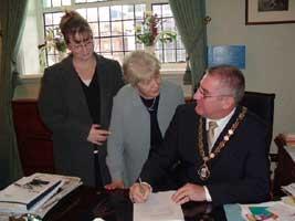 Sinn Féin's Joe O'Donnell with Kieran Milnes' mother Mary and sister Colleen in the Belfast Deputy Mayor's parlour