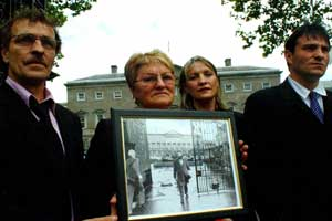 Dinah Fullerton and other family members outside Leinster House on Thursday carrying a photo of her husband leaving Leinster House in 1984