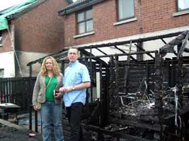 Tierna Cunningham and Gerry Kelly outside the child's playhouse gutted by loyalist arsonists