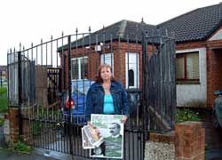 Frances McGrath stands outside her county council home, which she has had to turn into a fortress