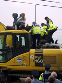 Protesters try to stop Gardaí using a JCB as a battering ram by climbing onto it