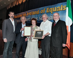 Pádraigín Uí Mhurchadha receives presentation from Martin Ferris TD.  Also in picture are Cllr. Seán Conlon, Pádraigín's husband Matt Murphy and Caoimhghín Ó Caoláin TD