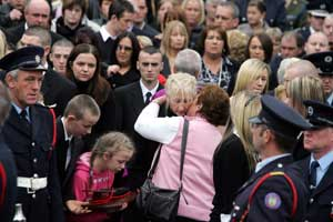 Mary Murray, the wife of Bray fire-fighter Brian Murray, is comforted by a friend at her husband's funeral