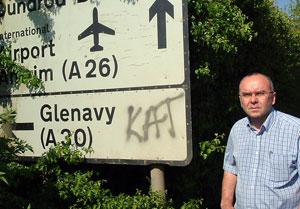 Paul Butler pictured beside sectarian graffiti which has been a regular feature of life in Stoneyford