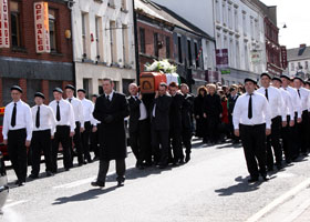 A republican honour guard escorts Seamus Trainor to his final resting place