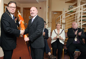 Alex Maskey presents Tom Hartley with the Tricolour