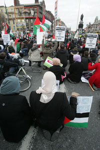 Protestors sit down on O'Connell Street Bridge during a rally in Dublin city centre over the Israeli Forces' onslaught against Gaza