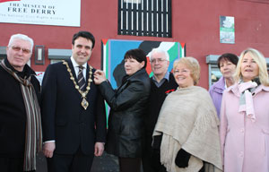 Mayor of Derry, Councillor Gerard Diver is being presented with a Bloody Sunday black ribbon by Mary Nash.  Also in photo are family members Leo Young, John Kelly, Kate Nash, Brigid Nash and Linda Nash