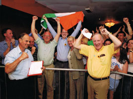 IN THE THICK OF IT: Tommy Devereux celebrates election victory for Cllr Noel Campbell (with Tricolour) and ex-POW Joe McHale with a clenched fist on one hand and a clipboard in the other