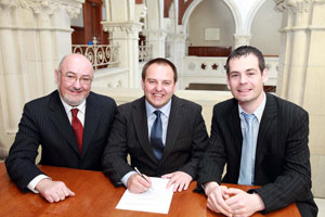 SIGNING UP FOR A FIGHT: Pádraig signs his nomination papers flanked by Caoimhghín Ó Caoláin TD and Senator Pearse Dohery