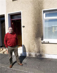 Mitchel outside his scorch damaged home, this was the third attack on his home in the past month