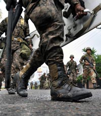 JACK-BOOT: Soldiers patrol a street near the presidential building in Tegucigalpa