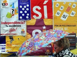 A woman walks past posters calling for the independence of Catalonia