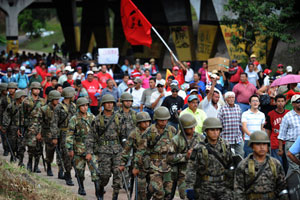 Honduran soldiers march next to supporters of the ousted president Manuel Zelaya during a protest near the Brazilian embassy