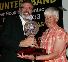 Gerry Adams makes a presentation of a piece of engraved crystal to Margaret McClenaghan